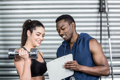 Athletic trainer explaining workout plan to woman stock photography