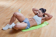 Athletic trainer show exercises in the gym. Beautiful athletic trainer shows examples of exercises in the gym Royalty Free Stock Images