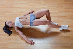 Athletic trainer shows examples of exercises. Beautiful athletic trainer shows examples of exercises in the gym Stock Photos