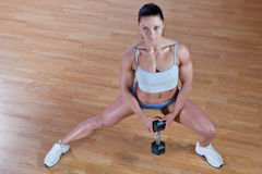 Athletic trainer shows examples of exercises. Beautiful athletic trainer shows examples of exercises in the gym Royalty Free Stock Image