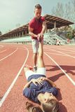 Athletic trainer while stretching muscles of a young runner. `s leg on the track Stock Photo