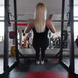 Athletic trainer of a young woman in black sportswear in gym sneakers. Girl doing exercises in a fitness studio. Back view. stock photos