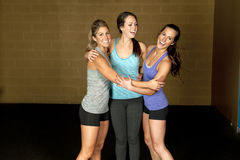 Athletic Trainers in Gym. A set of three happy brunette atheltic females posing in a gym together stock image