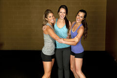 Athletic Trainers in Gym. A set of three happy brunette atheltic females posing in a gym together stock photos