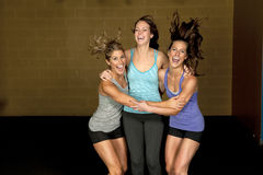 Athletic Trainers in Gym. A set of three happy brunette atheltic females posing in a gym together stock images