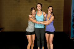 Athletic Trainers in Gym. A set of three happy brunette atheltic females posing in a gym together stock photo