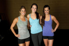 Athletic Trainers in Gym. A set of three happy brunette atheltic females posing in a gym together royalty free stock images