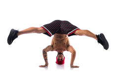 Athletic trendy shirtless young man doing break dance routine. Athletic trendy shirtless young man in a hat doing a break dance routine isolated on white Stock Image