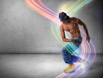 Athletic trendy young man doing a break dance routine. Athletic trendy shirtless young man in a hat doing a break dance routine surrounded by colorful light Stock Photography