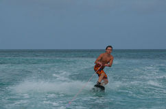 Athletic Wakeboarder in a Crouch off the Coast of Aruba Royalty Free Stock Photo
