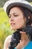 Athletic woman adjusting her bike helmet Royalty Free Stock Photos