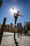 Athletic woman balancing on bollard and holding her leg Stock Photos