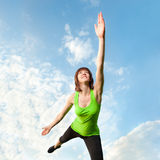 Athletic woman balancing in front of blue sky Royalty Free Stock Image