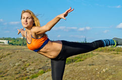 Athletic woman balancing on one leg Royalty Free Stock Images