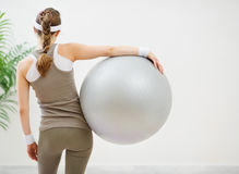 Athletic woman with ball standing back to camera Royalty Free Stock Image