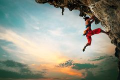 Free Athletic Woman Climbing On Overhanging Cliff Rock With Sunset Sky Background Royalty Free Stock Images - 165935879