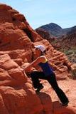 Athletic Woman climbing on rock Stock Photo