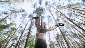 Athletic woman, coach, instructor, performs, doing exercises with fitness trx system, TRX suspension straps. In pine stock video