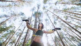 Athletic woman, coach, instructor, performs, doing exercises with fitness trx system, TRX suspension straps. In pine stock video footage