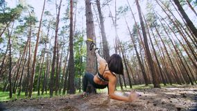 Athletic woman, coach, instructor, performs, doing exercises with fitness trx system, TRX suspension straps. In pine. Athletic, woman, coach, instructor stock video