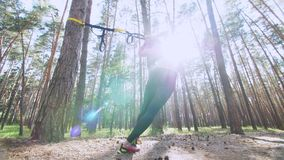 Athletic woman, coach, instructor, performs, doing exercises with fitness trx system, TRX suspension straps. In pine. Athletic, woman, coach, instructor stock video footage