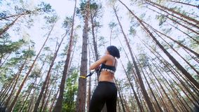 Athletic woman, coach, instructor, performs, doing exercises with fitness trx system, TRX suspension straps. In pine stock footage