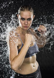 Athletic Woman in Combat Pose in Water Splashes royalty free stock image