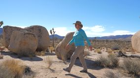 Athletic Woman In A Cowboy Hat Goes On A Mojave Desert, Jumps Through The Bushes. Woman in a cowboy hat, sunglasses and protective outdoor clothes. Walking stock video