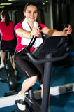 Athletic woman cycling at the gym. Happy athletic woman on exercise bike at the fitness centre Stock Photography