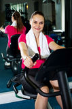 Athletic woman cycling at the gym Stock Photos