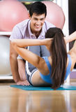 Athletic woman does situps with coach. Athletic women does situps with coach in training gym Royalty Free Stock Photography