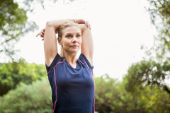 Athletic woman doing arms stretching stock image