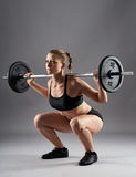 Athletic woman doing barbell squats Stock Image