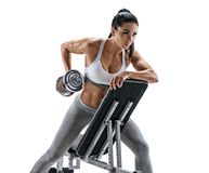 Athletic woman doing exercise with dumbbell leaning on sports bench. Photo of latin woman in fashionable sportswear isolated on white background. Strength and Stock Image