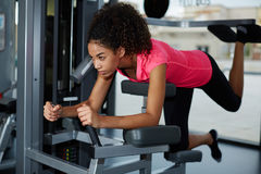 Athletic woman doing exercise for legs and buttocks on press machine at gym. Full length portrait of athletic woman doing exercise for legs and buttocks on press Royalty Free Stock Images
