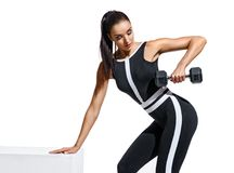 Athletic woman doing exercises with dumbbells for hands. Photo of fitness model in black sportswear isolated on white background. Strength and motivation Royalty Free Stock Photography