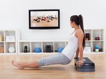 Athletic woman doing exercises in her livingroom Royalty Free Stock Image