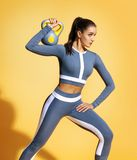 Athletic woman doing exercises with a kettlebell. Photo of latin woman in grey sportswear on yellow background. Strength and motivation Royalty Free Stock Images