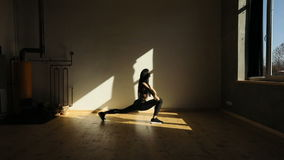 The athletic woman is doing lunges and jumping while changing the legs. The studio location. stock footage