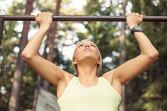 Athletic woman doing pull up Stock Images