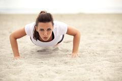 Athletic Woman Doing Push Up on the Beach Royalty Free Stock Photos