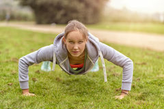Athletic Woman Doing Push Up Exercise at the Park Stock Photo