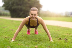 Athletic Woman Doing Push Up Exercise at the Park Royalty Free Stock Photo