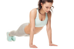 Athletic woman doing push-ups on a white background Stock Image