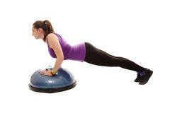 Athletic woman doing pushups on a bosu ball Royalty Free Stock Photography