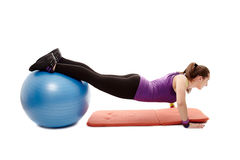 Athletic woman doing pushups with legs on the ball Stock Photos