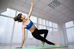 Athletic woman doing side plank at yoga studio royalty free stock image