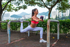 Athletic woman doing single leg split squat exercise with park equipment outdoors  high buildings in background Royalty Free Stock Images