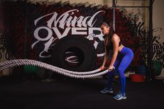 Athletic woman doing some crossfit exercises with a heavy rope stock photography