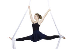 Athletic woman doing some tricks on silks. Pretty woman - aerialist doing acrobatic tricks on aerial silks Stock Images